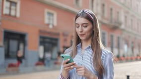 Smiling young woman wearing in blue and white striped dress shirt walking around old street using smartphone stock video footage
