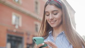 Smiling young woman wearing in blue and white striped dress shirt walking around old street using smartphone stock video