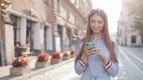 Smiling young woman wearing in blue and white striped dress shirt walking around old street using smartphone stock footage
