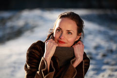 Smiling young woman wearing a buckskin jacket. Beautiful young woman in a park in winter time stock image