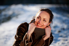Smiling young woman wearing a buckskin jacket. Beautiful young woman in a park in winter time royalty free stock images