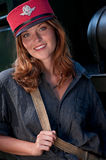 Smiling young woman wearing conductor's cap Stock Images