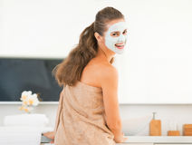Smiling young woman wearing facial cosmetic mask Stock Photo