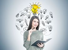Smiling woman with a planner, many ideas. Smiling young woman wearing a gray sweater is holding a planner and a pen. Yellow light bulbs on a gray wall. An idea stock photo