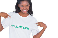 Smiling young woman wearing volunteer tshirt and pointing to it Royalty Free Stock Image