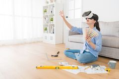 Smiling young woman wearing VR technology goggles. Viewing new house design sketch drawing and touching simulation screen to choose color Stock Images