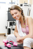 Smiling young woman weightlifting at the gym and looking at came Stock Images