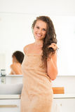 Smiling young woman with wet hair in bathroom Stock Images