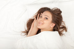 Smiling young woman in white bedding Royalty Free Stock Image