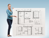 Smiling young woman with white board and blueprint Royalty Free Stock Photography