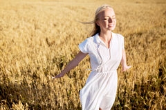 Smiling young woman in white dress on cereal field Royalty Free Stock Image