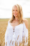 Smiling young woman in white dress on cereal field Royalty Free Stock Photos