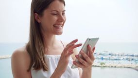 Woman using mobile on balcony. Female on vacation chatting with friend via cellphone in slow motion. Smiling young woman in white dress using mobile on balcony stock footage