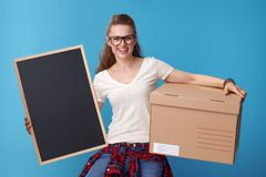 Smiling woman with cardboard box showing blank board on blue Royalty Free Stock Photography