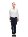 Smiling young woman in white shirt and jeans Royalty Free Stock Image