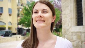 Smiling young woman in white t-shirt walk down street in european city in slow motion. Looking around stock video