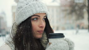 Smiling young woman in white warm clothes with and drinking coffee to take away over snowy city background stock video