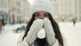 Smiling young woman in white warm clothes with and drinking coffee to take away over snowy city background stock footage