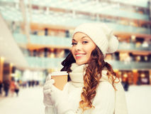 Smiling young woman in winter clothes with cup Royalty Free Stock Photo