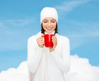 Smiling young woman in winter clothes with cup Royalty Free Stock Image