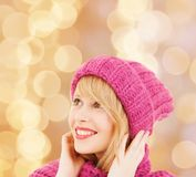 Smiling young woman in winter clothes. Happiness, winter holidays, christmas and people concept - smiling young woman in pink hat and scarf over beige lights stock image