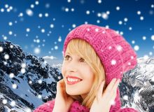 Smiling young woman in winter clothes. Happiness, winter holidays, christmas and people concept - smiling young woman in pink hat and scarf over blue snowy royalty free stock images