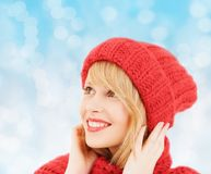 Smiling young woman in winter clothes. Happiness, winter holidays, christmas and people concept - smiling young woman in red hat and scarf over blue lights stock photography
