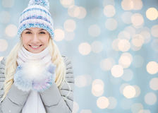 Smiling young woman in winter clothes over lights Royalty Free Stock Photo