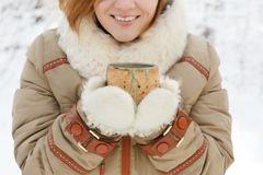 Smiling young woman in winter coat and white fluffy mittens hold Royalty Free Stock Photos