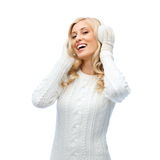 Smiling young woman in winter earmuffs and sweater Stock Photo