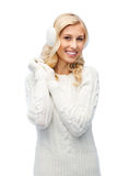 Smiling young woman in winter earmuffs and sweater Stock Images