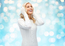 Smiling young woman in winter earmuffs and sweater Royalty Free Stock Photography