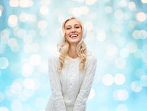 Smiling young woman in winter earmuffs and sweater Royalty Free Stock Images