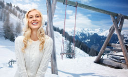 Smiling young woman in winter earmuffs and sweater Royalty Free Stock Image