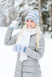Smiling young woman in winter forest Royalty Free Stock Image