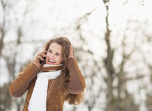 Smiling young woman in winter park talking mobile phone Royalty Free Stock Photos