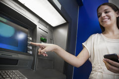 Smiling young woman withdrawing money from the ATM Stock Image