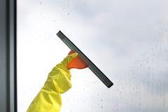 Worker cleaning soap suds on glass window with squeegee and rag stock images