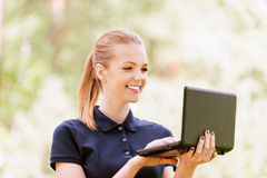 Smiling young woman working on Stock Photo