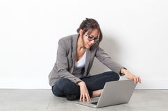 Smiling young woman working on computer relaxing on the floor Stock Images