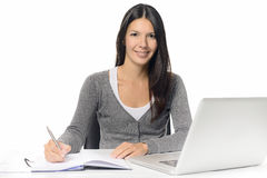 Smiling young woman working at a desk royalty free stock photos