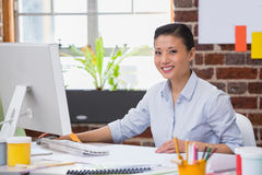Smiling young woman working at desk Royalty Free Stock Images
