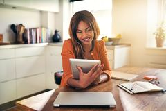 Smiling young woman working from home with a digital tablet. Young African woman sitting at her kitchen table at home smiling while working on her online stock photos