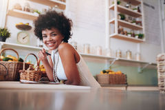 Smiling young woman working in a juice bar. Portrait of smiling young woman working in a juice bar. African female standing behind the counter looking at camera Royalty Free Stock Image