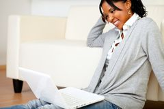 Smiling young woman working on laptop. Portrait of a smiling young woman working laptop while is sitting on the floor Stock Photo