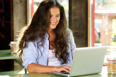 Smiling young woman working on laptop at cafe Stock Photos