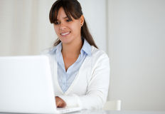 Smiling young woman working on laptop computer Royalty Free Stock Images