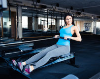 Smiling young woman working out on simulator Stock Photography