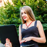 Smiling young woman works with laptop outdoors Stock Image