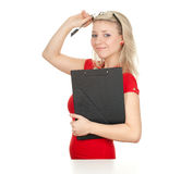 Smiling young woman  writing on black clipboard Royalty Free Stock Image